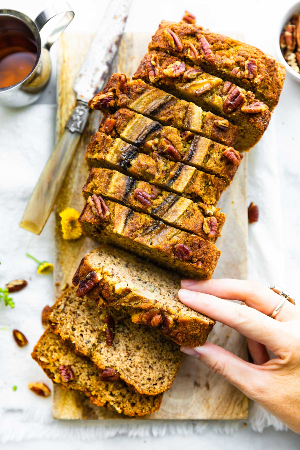 woman pulling slice of healthy banana nut bread from sliced loaf on wooden tray