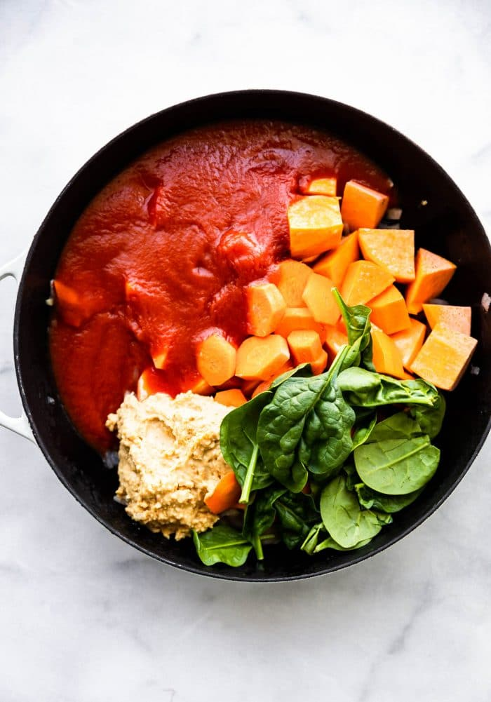 overhead photo: tomato sauce, spinach leaves and chunks of sweet potato in black pot