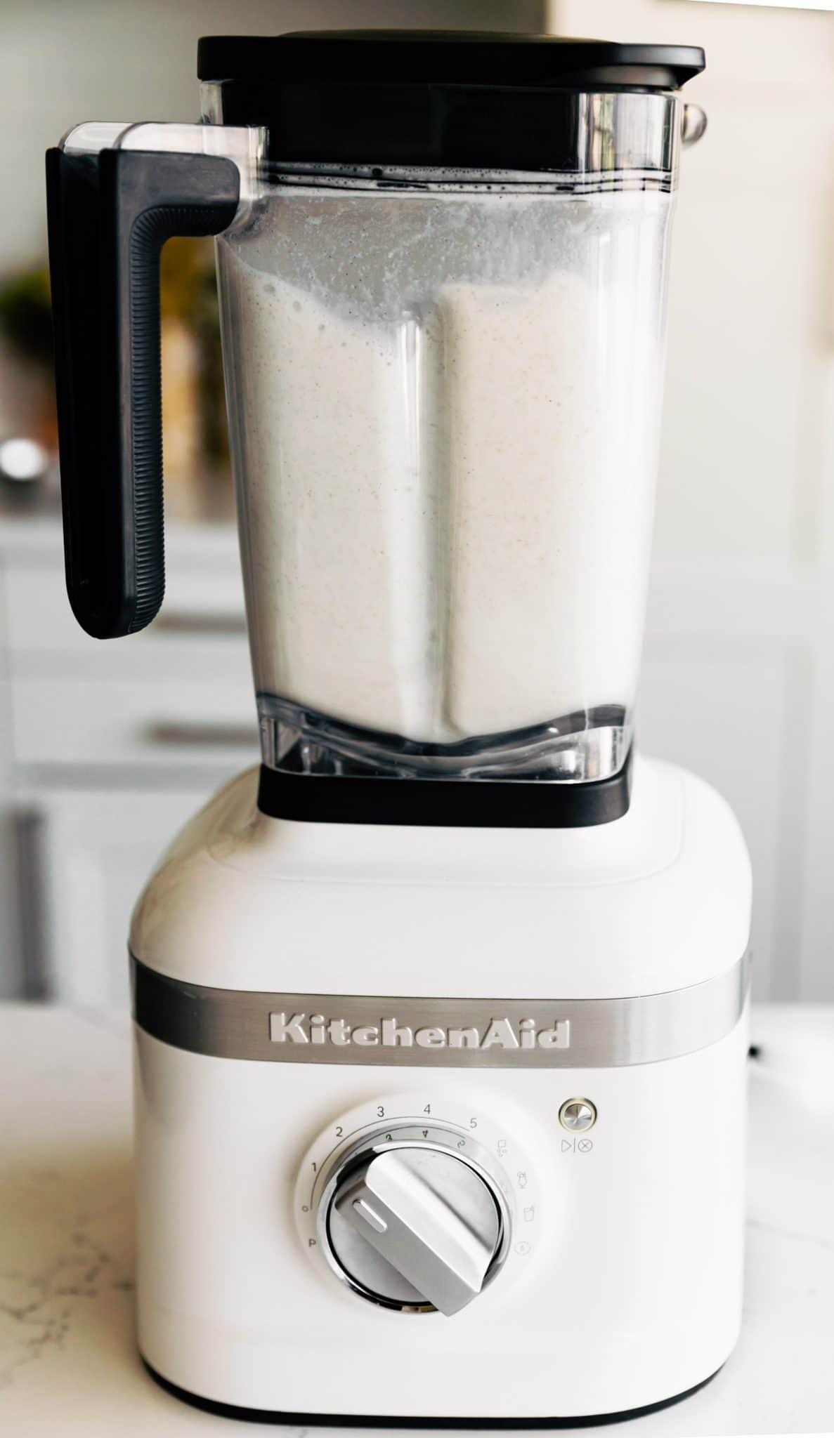 image shows how to make hemp milk in a white KitchenAid blender
