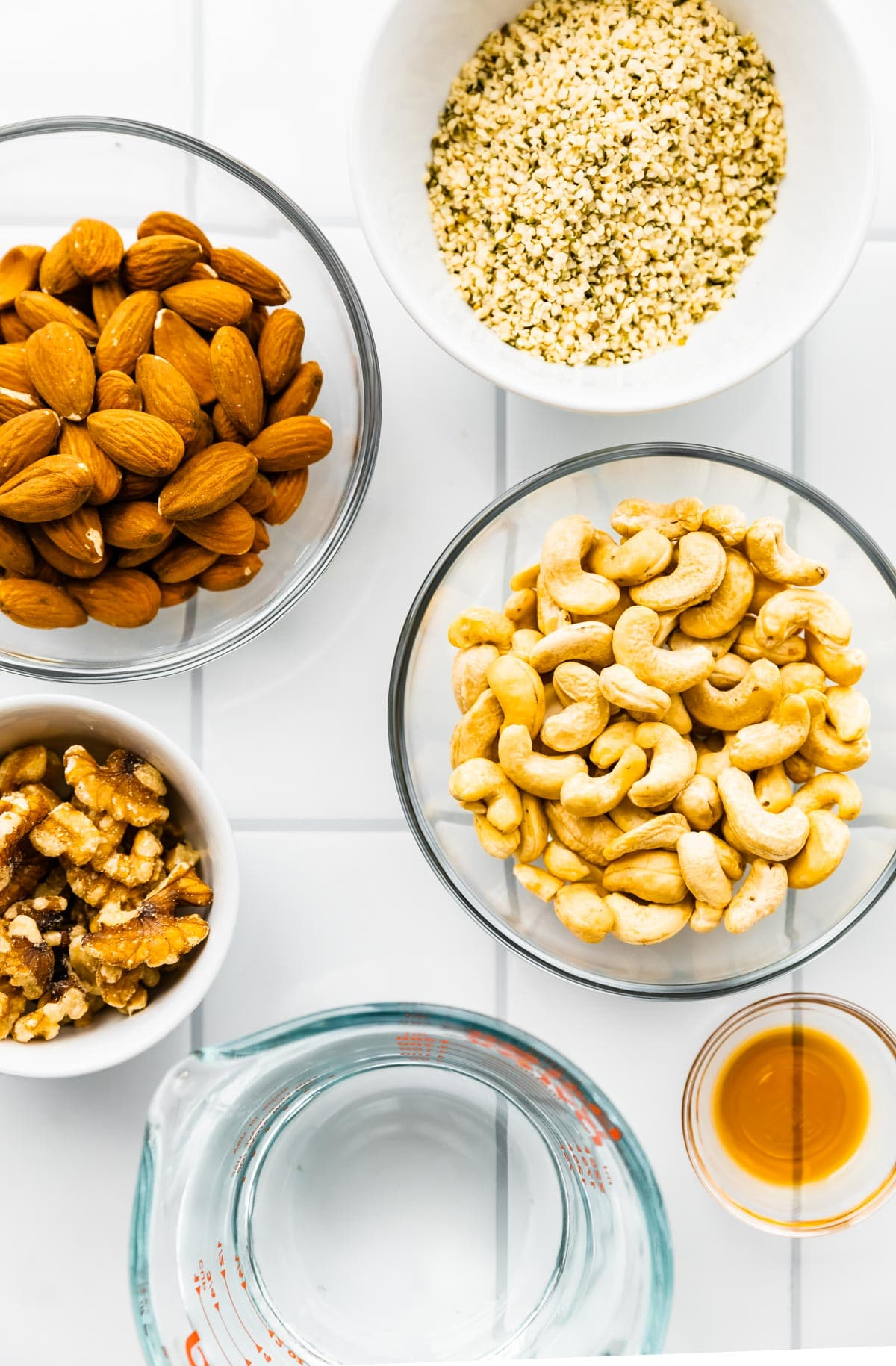 overhead image: bowls of raw cashews, almonds, walnuts, and hemp seed