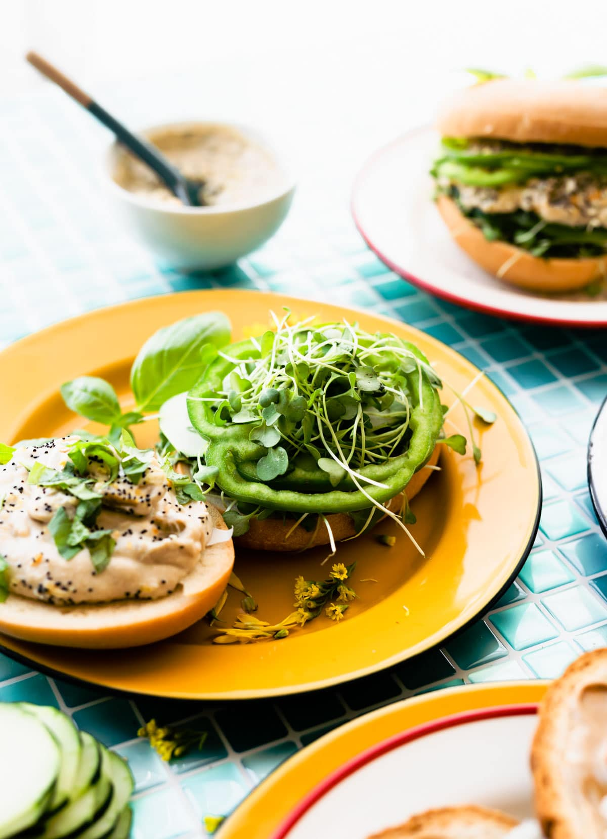 gluten free bagel on yellow plate topped with healthy green ingredients