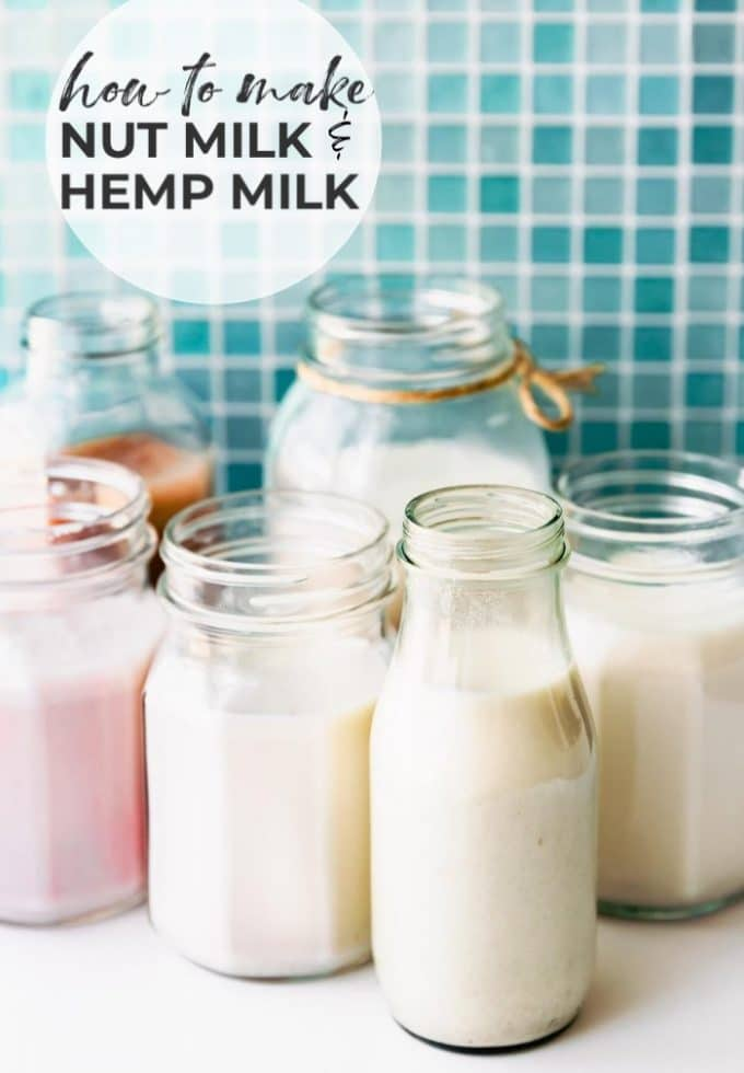 small glass bottles and mason jars filled with cashew milk, hemp milk, and almond milk