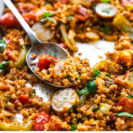 baked Mexican cauliflower rice with chorizo on a sheet pan, with some on a serving spoon