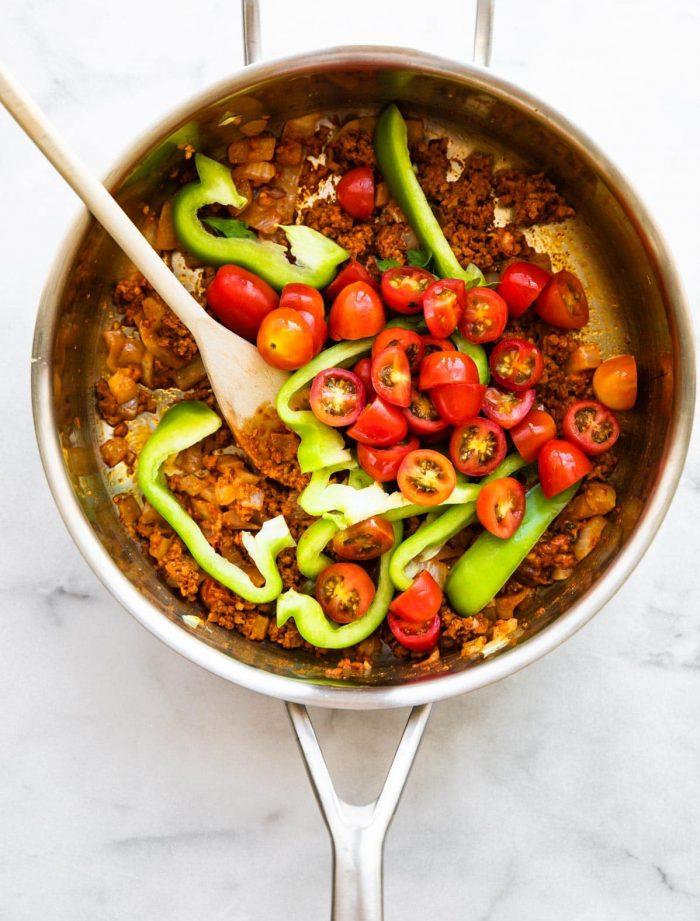overhead photo: sliced cherry tomatoes and green bell pepper slices in skillet with crumbled chorizo