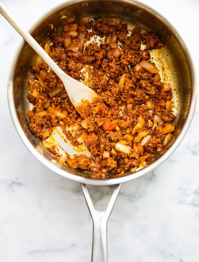 overhead photo: wooden spoon in large skillet with ground chorizo