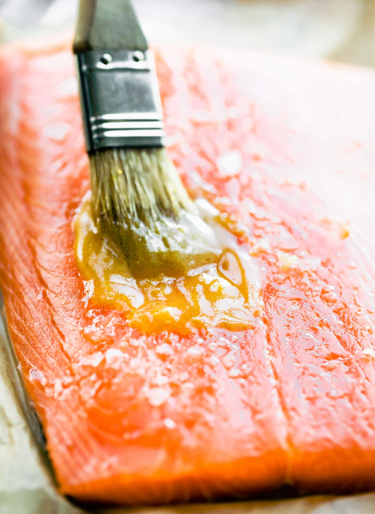 brushing melted butter onto piece of raw salmon