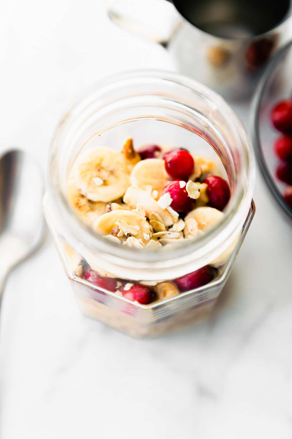 pumpkin overnight oats topped with banana slices and cranberries in mason jar