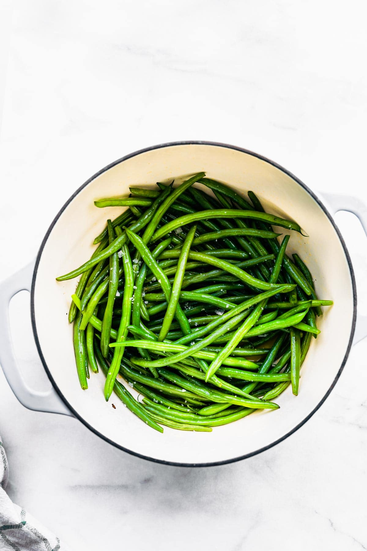 overhead photo: fresh green beans in white serving bowl