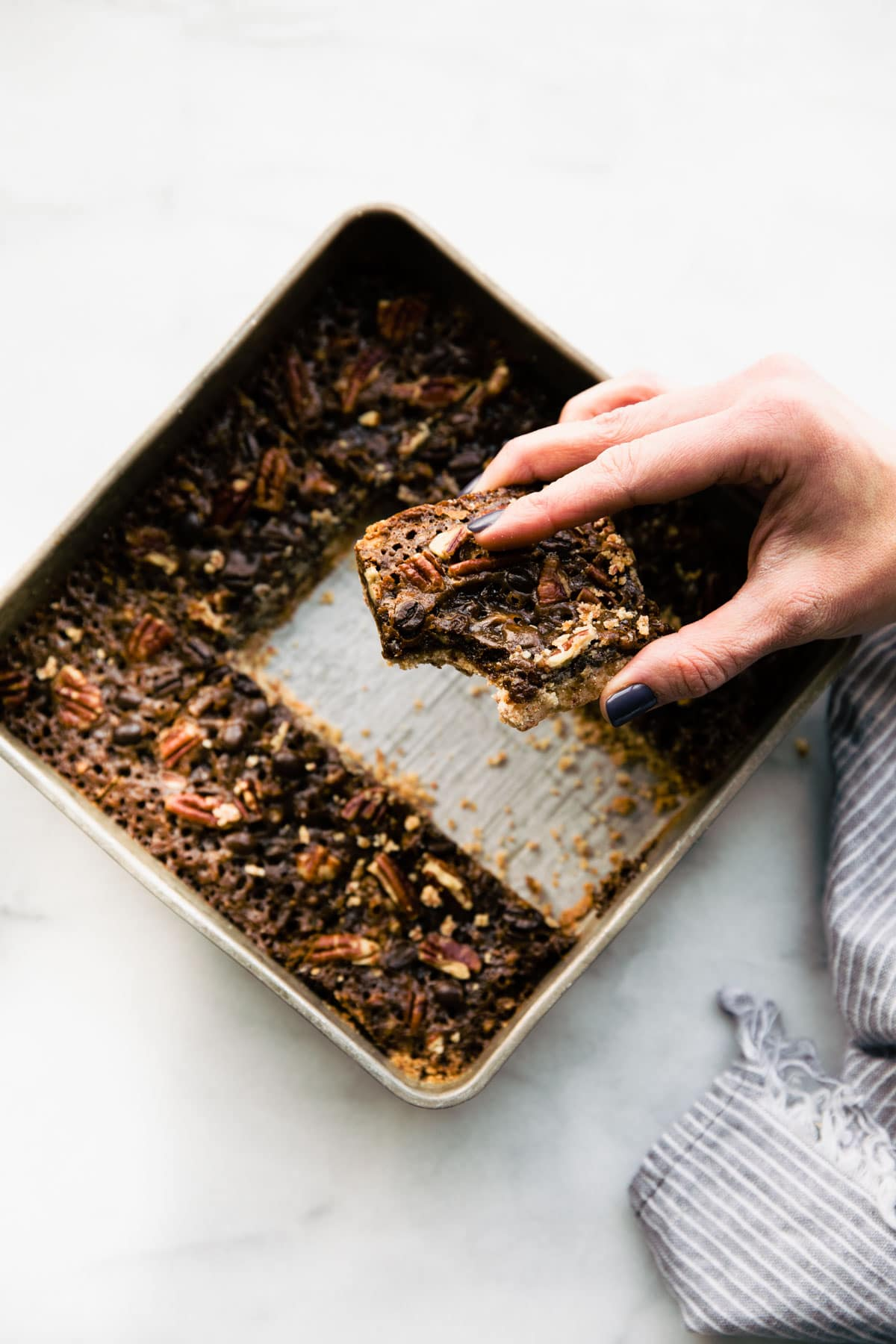 woman's hand holding a coffee-infused pecan pie bar above a pan of them