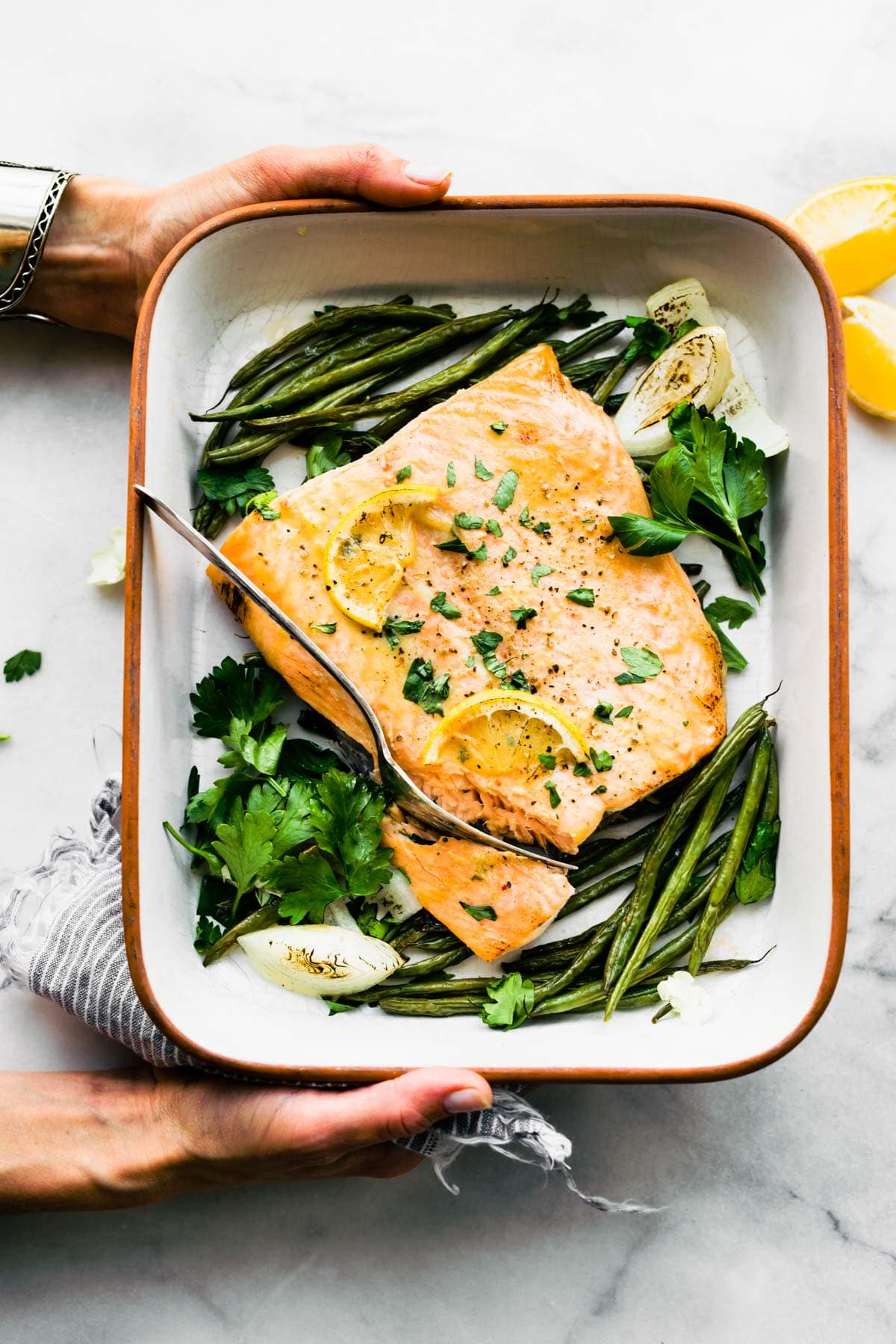 overhead photo: maple mustard baked salmon in white baking dish with French green beans
