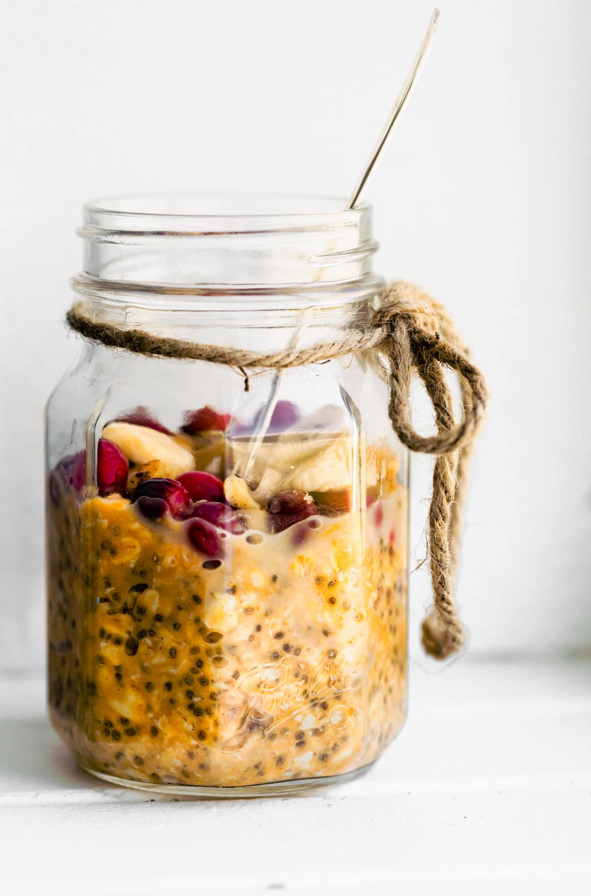 healthy cranberry-pumpkin overnight oats in mason jar with a spoon