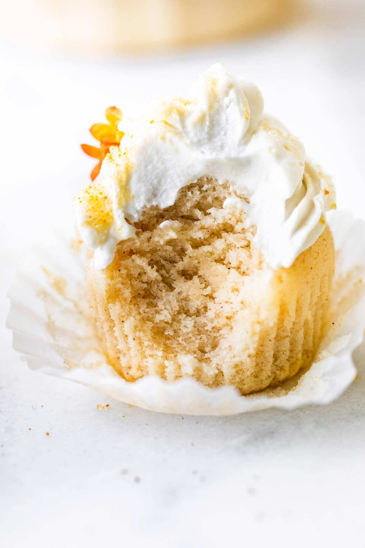 vanilla cupcake with frosting (bite removed from it
