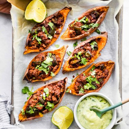 overhead photo: hands holding parchment paper lined tray of sweet potato skins filled with chili