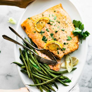 overhead: woman's hands holding plate of maple mustard salmon with French green beans