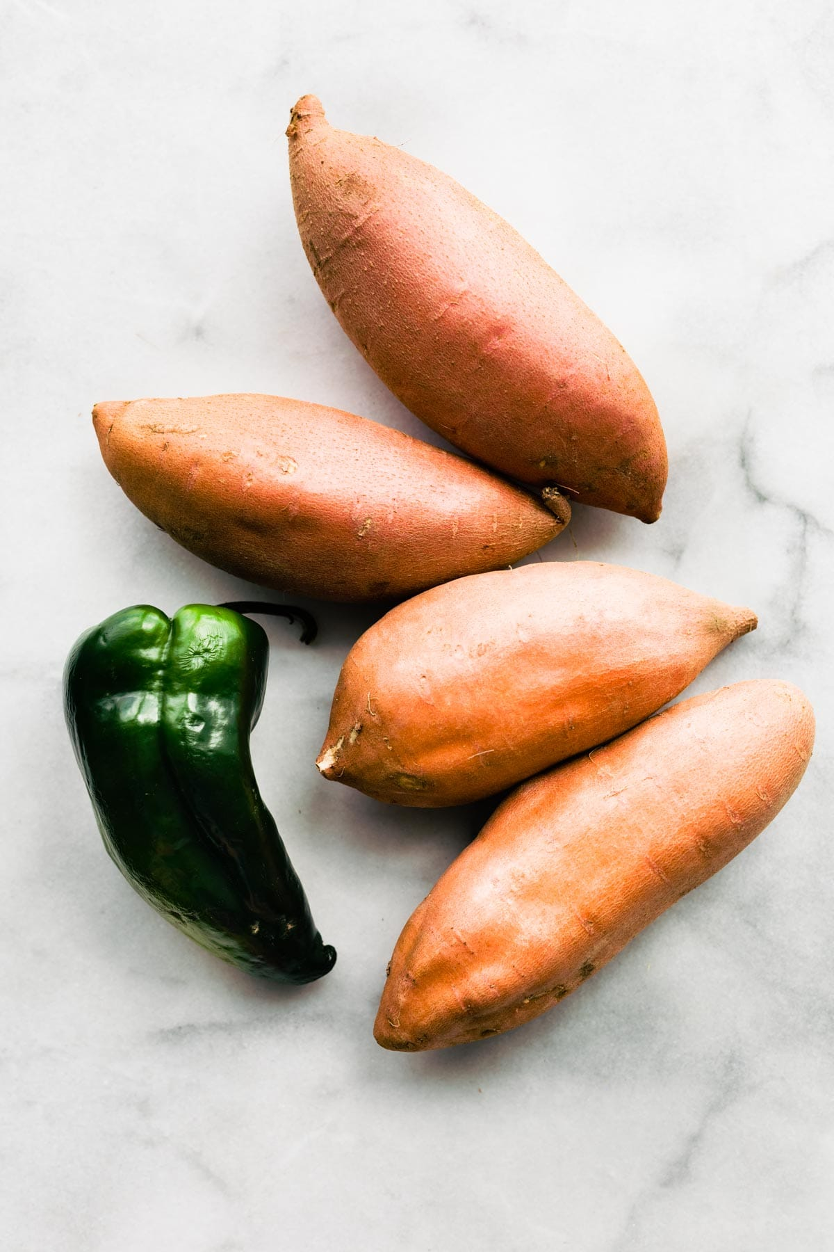overhead photo: 4 whole sweet potatoes and 1 poblano pepper on white marble background