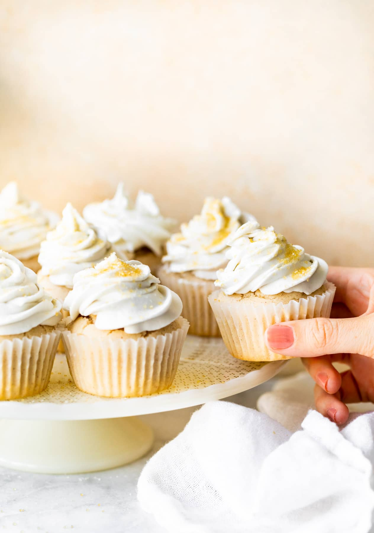 woman's hand removing frosted cupcake from group of them on cake stand
