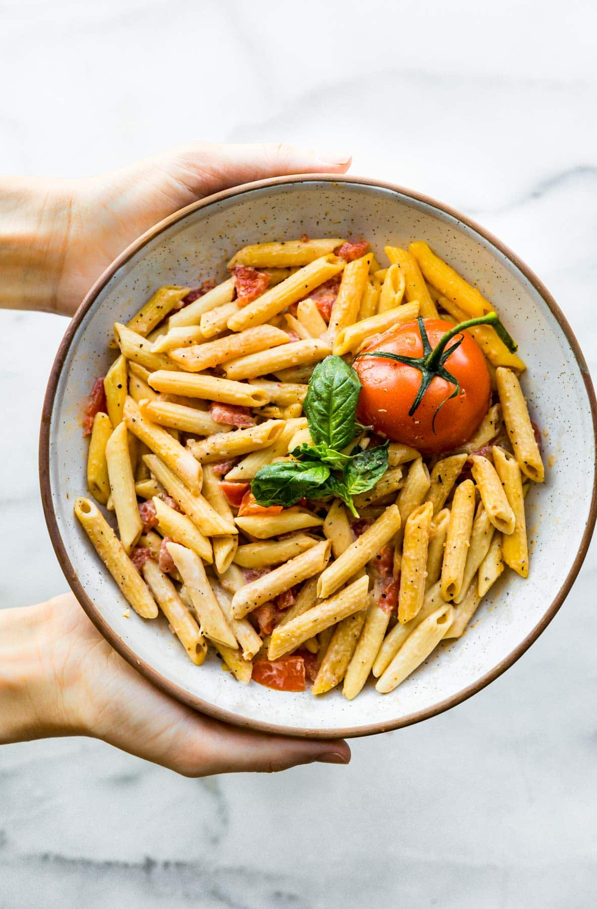 overhead image white bowl of: gluten free pasta (penne pasta) with pieces of fresh tomato and basil
