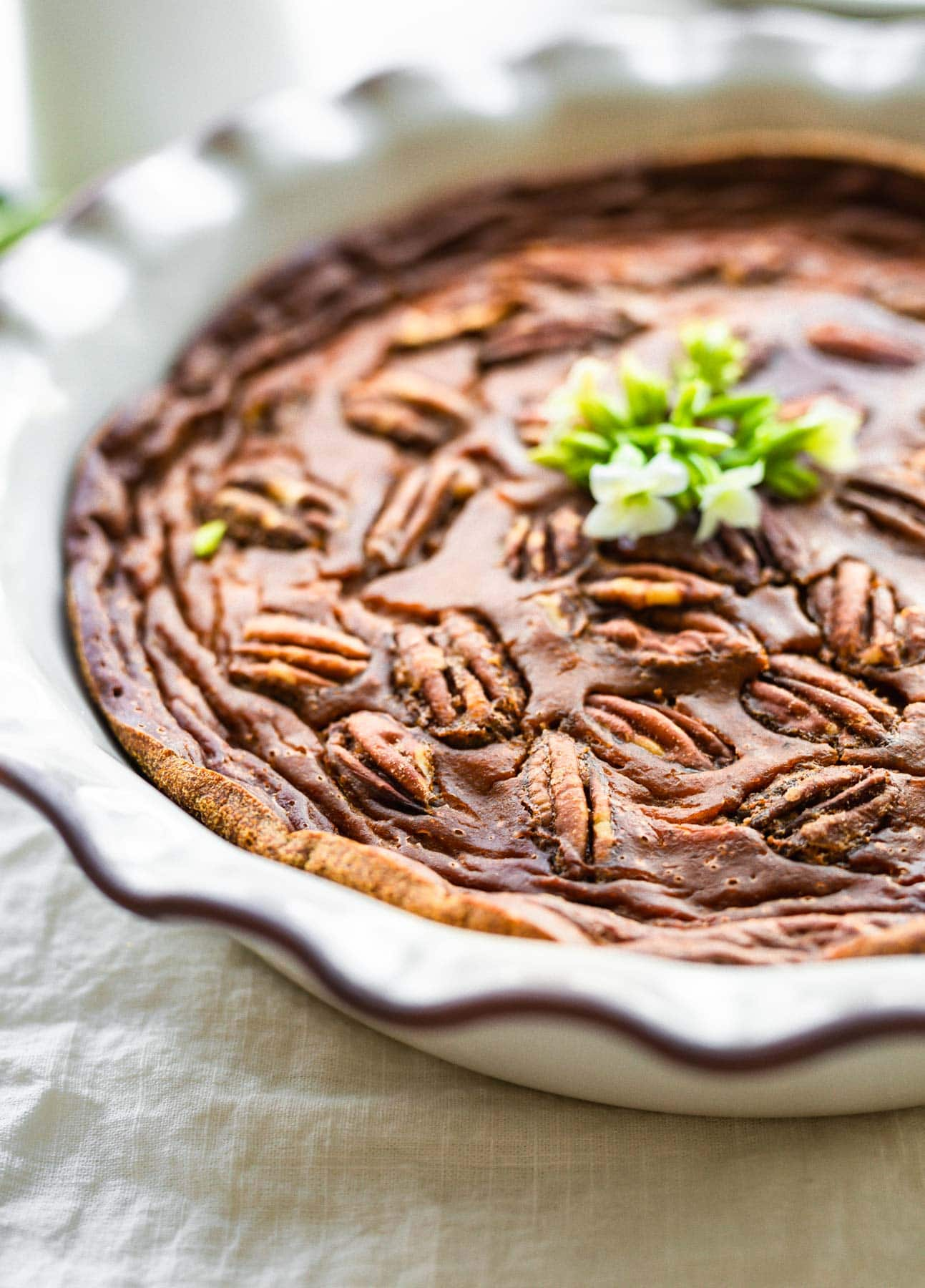 close up image: crustless sweet potato pie topped with pecans