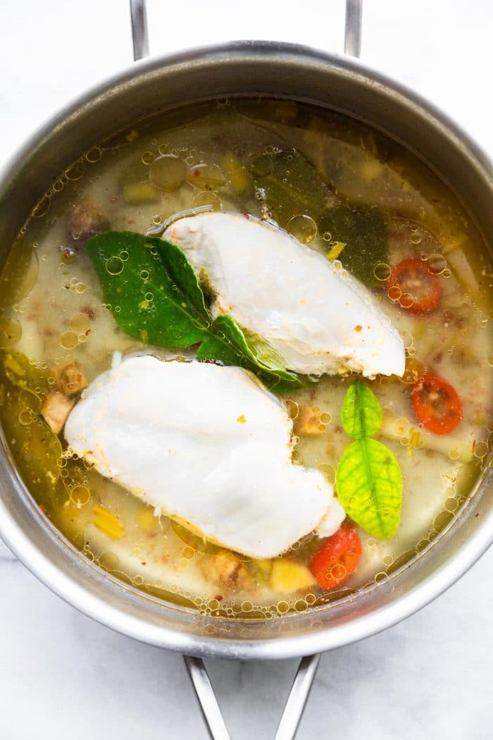 making Asian soup recipe in large pot with poached chicken and fresh herbs