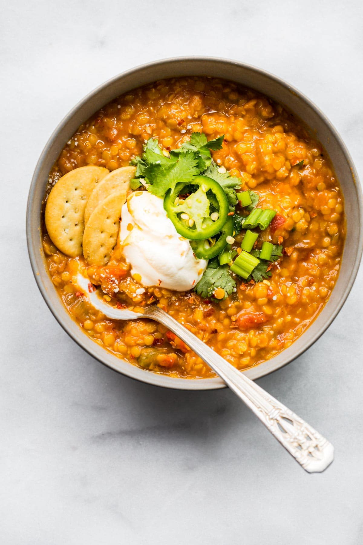overhead photo: spoon in bowl of slow cooker chili garnished with crackers, jalapeno slices and sour cream