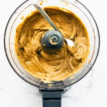 overhead: spoon in the bowl of a food processor, scooping creamy seed butter out