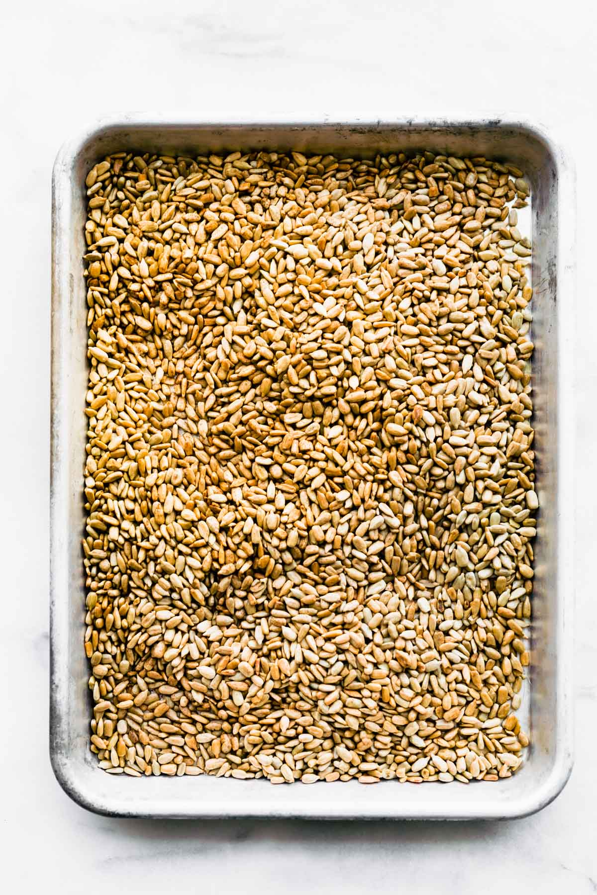overhead photo: raw sunflower seeds on baking sheet