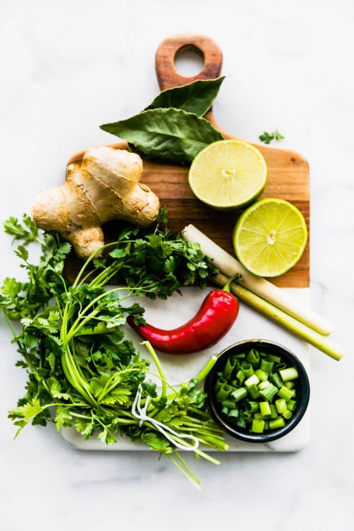 ginger root, lime halves, scallions, red chili pepper, and fresh herbs on cutting board