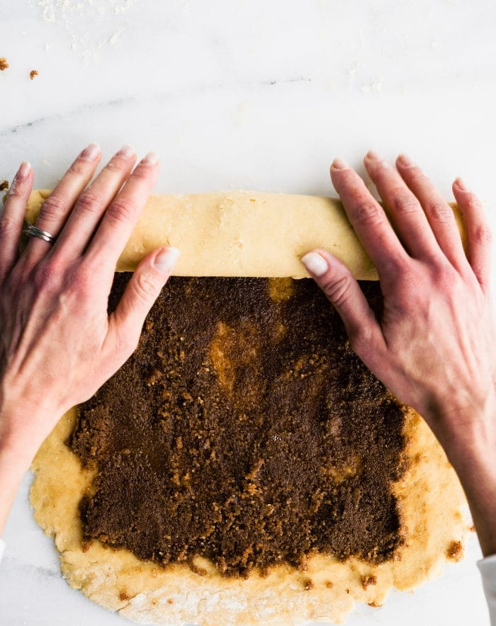 woman's hands rolling pastry dough coated with cinnamon and brown sugar