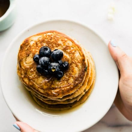 overhead photo: plated stack of vegan protein pancakes topped with fresh blueberries