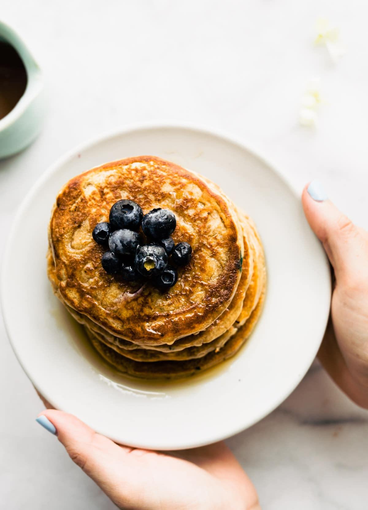 overhead shot: vegan protein pancakes topped with fresh blueberries on white plate