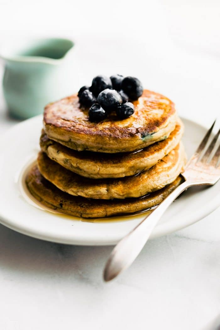 a stack of dairy free pancakes topped with fresh berries