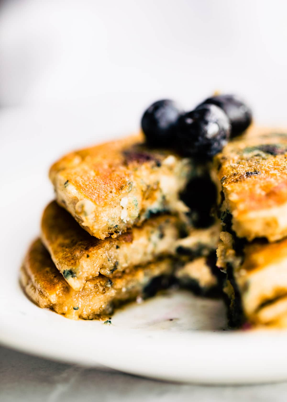 plated stack of fluffy homemade blueberry pancakes with blueberries on top