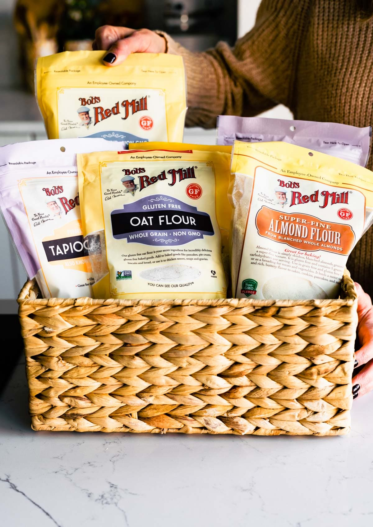 basket full of Bob's Red Mill gluten free baking products . Woman grabbing one bag with one hand
