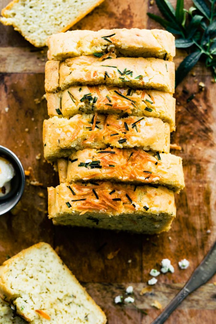 gluten free potato bread (mashed potato bread) sliced on wood board with herbs on top