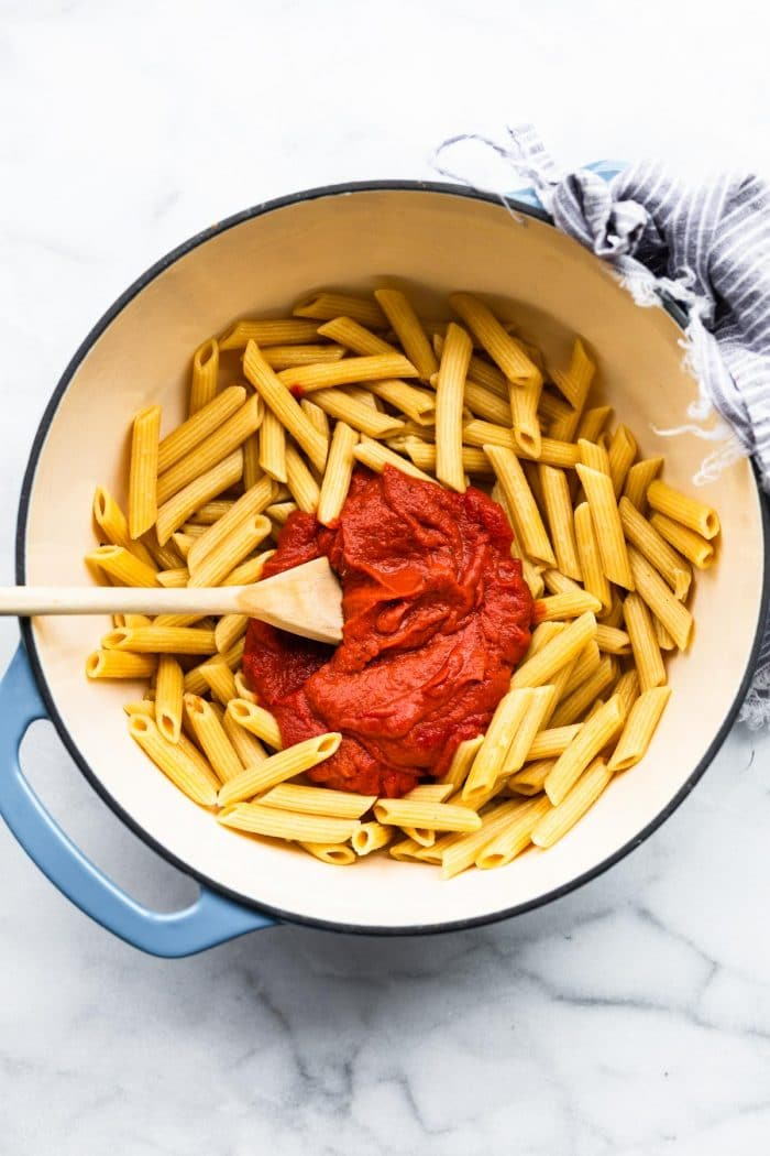 stirring red pepper sauce in large pot of penne pasta