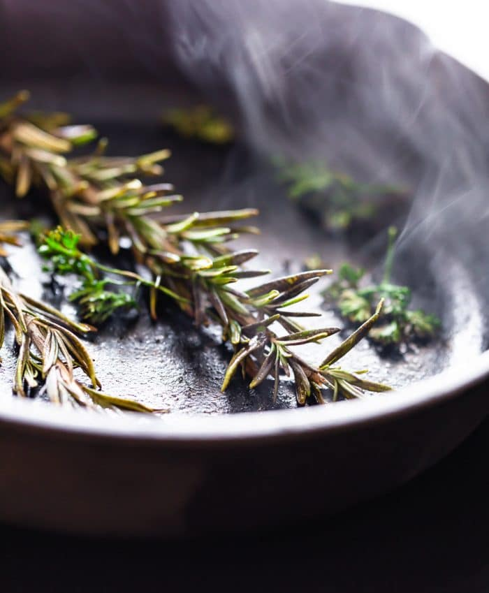 closeup: dry charring fresh rosemary in a skillet