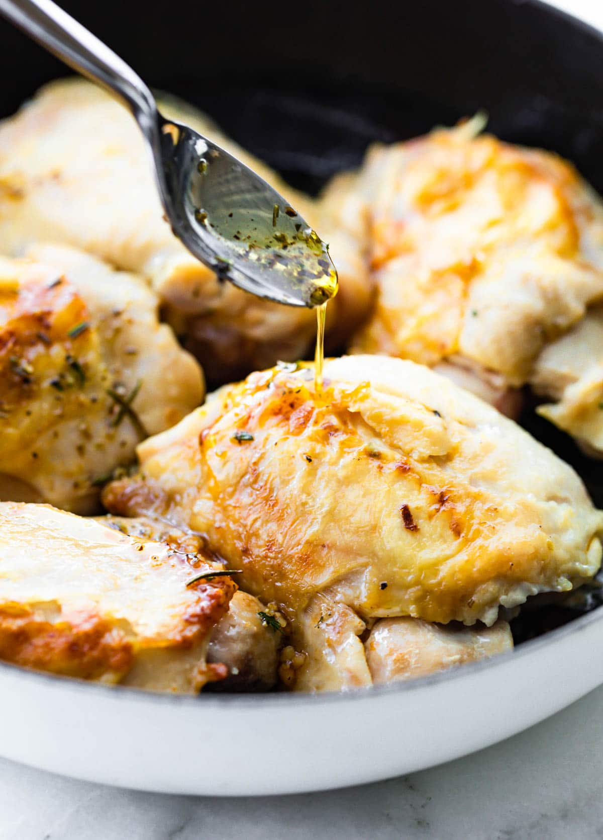 closeup: Greek dressing pouring off a spoon onto piece of roast chicken