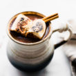Mexican hot chocolate cocktail in a mug garnished with cinnamon stick and toasted marshmallows