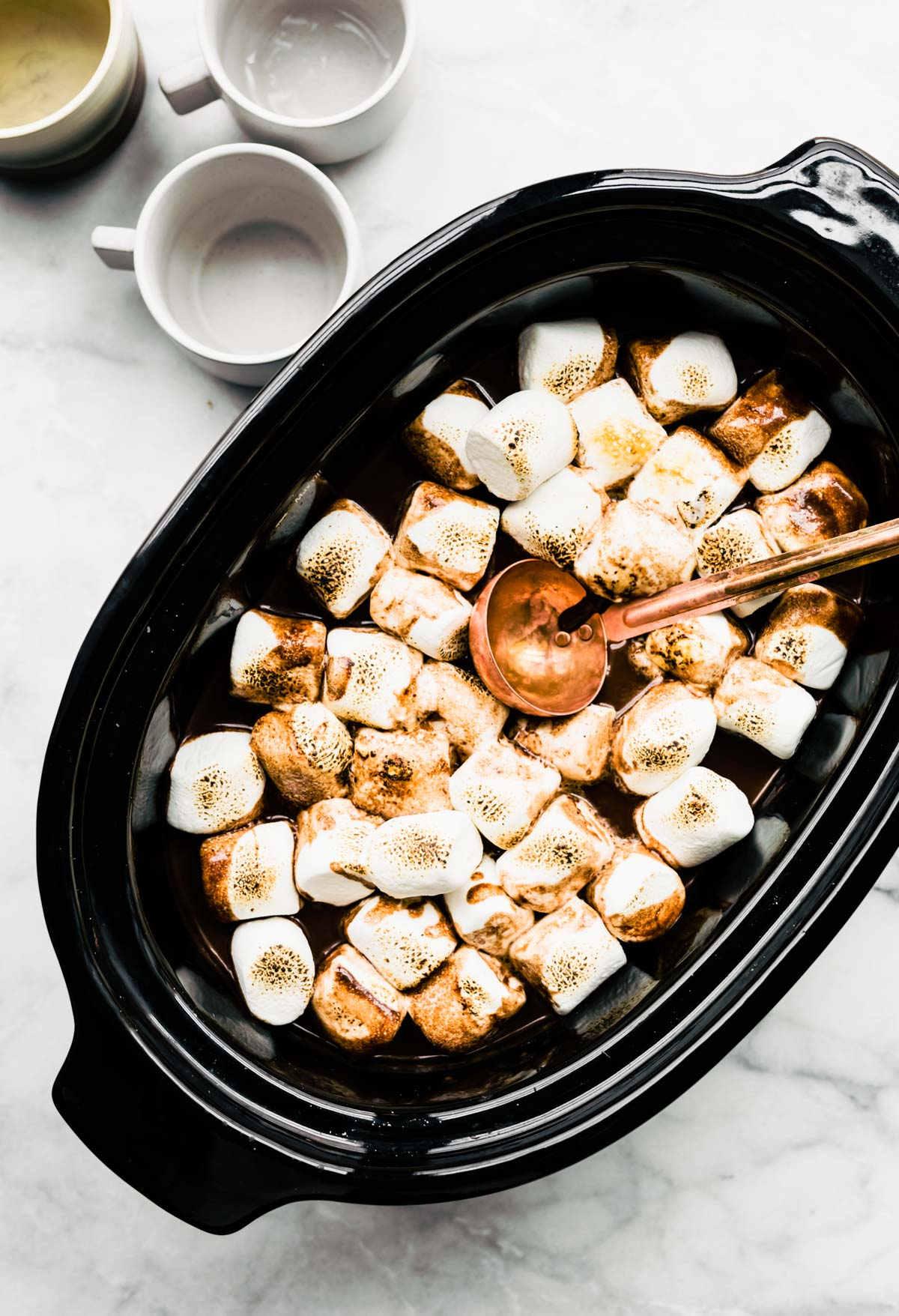 toasted marshmallows and a small ladle rest on top of a slow cooker full of spiked hot chocolate