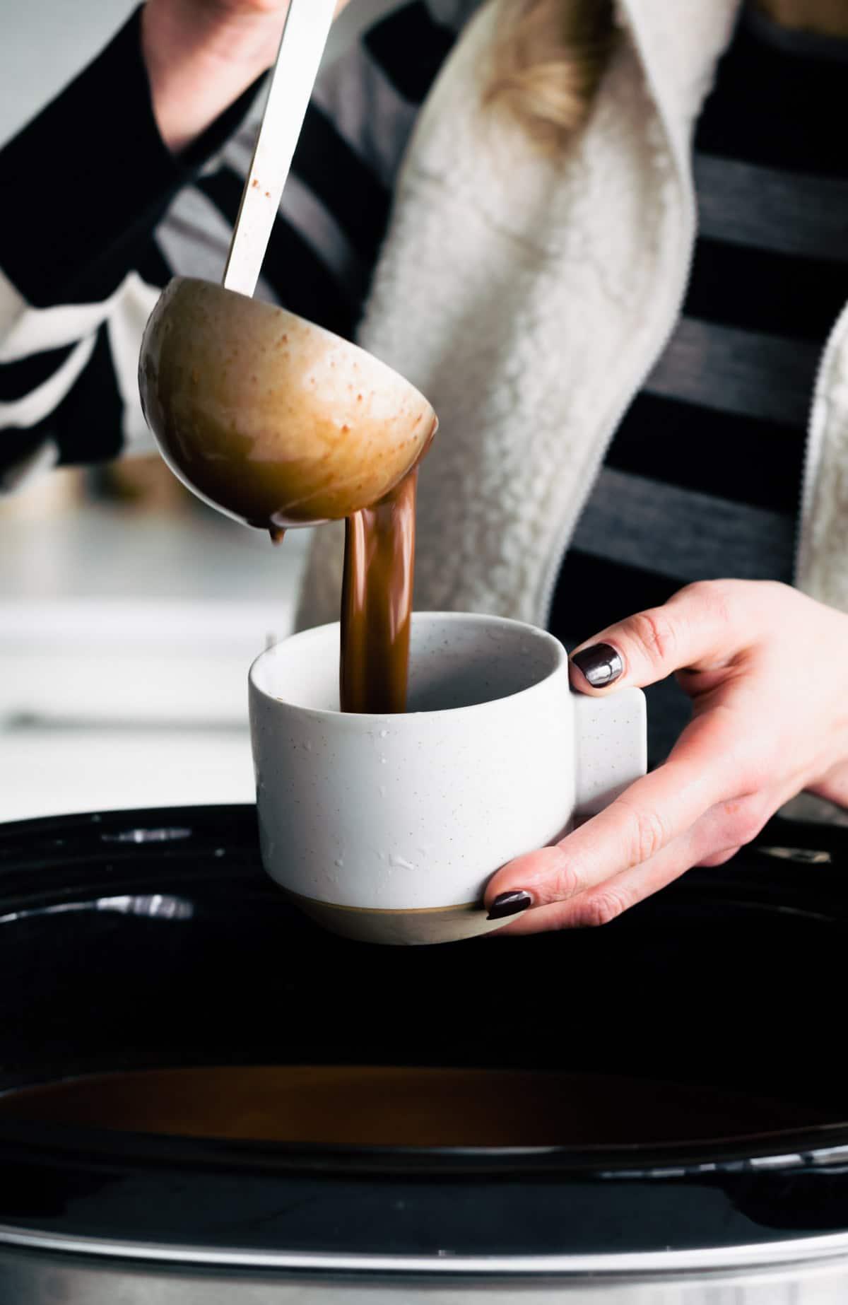 ladling hot chocolate from crockpot into a mug
