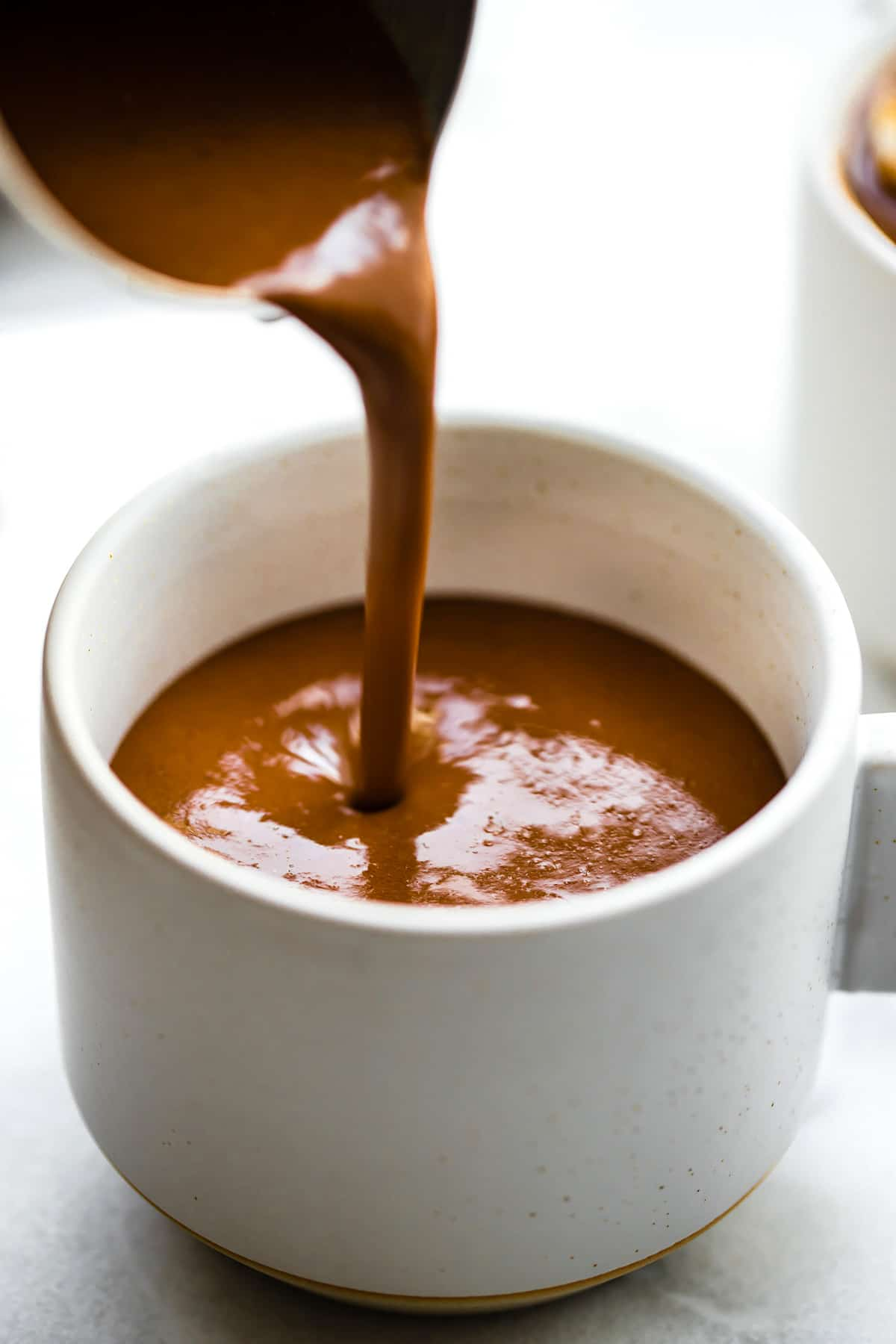 closeup: hot creamy drinking chocolate falling from ladle into a white mug