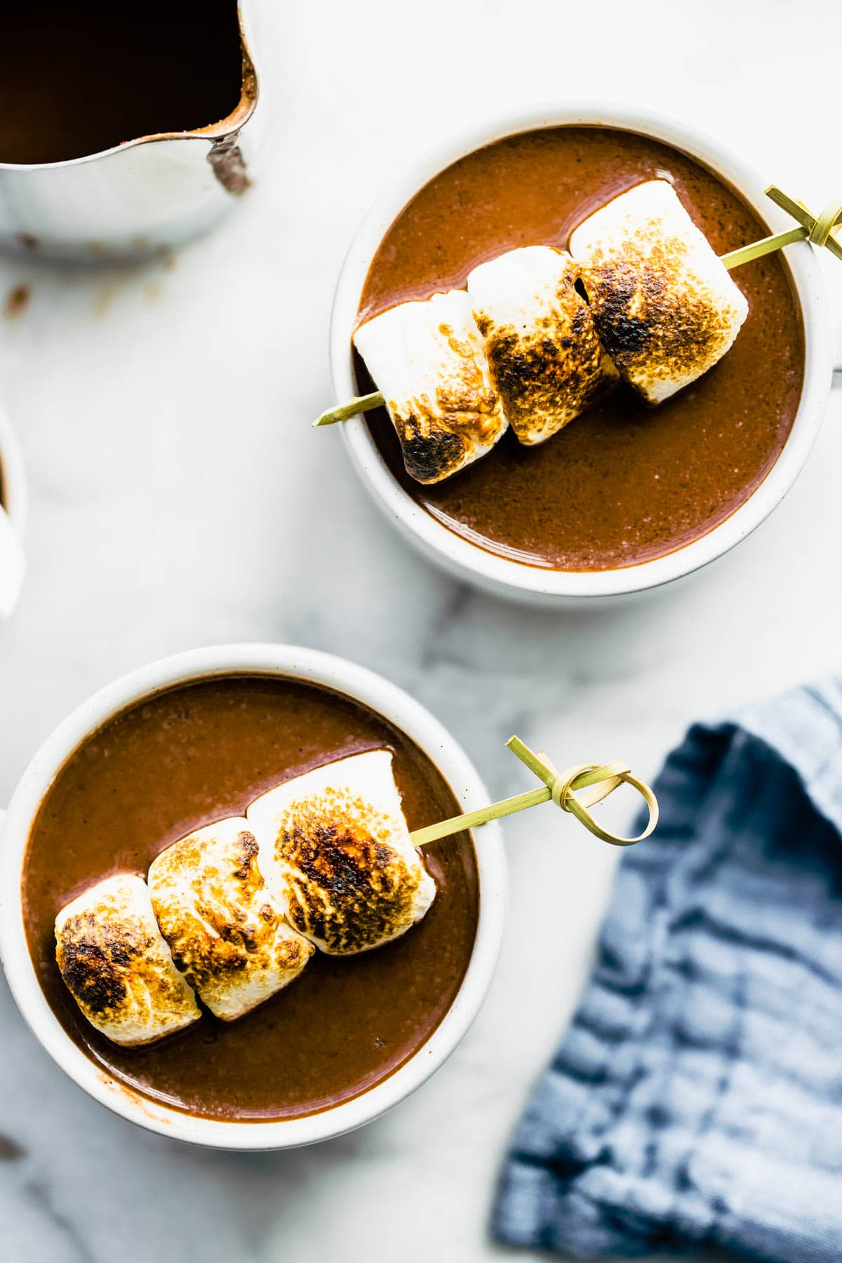 two boozy hot chocolate drinks with skewers of toasted marshmallows