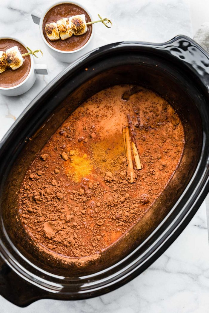 cocoa powder, non dairy milk, and cinnamon sticks in a slow cooker
