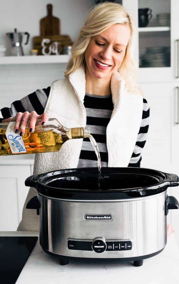 woman smiling as she pours liqueur into a slow cooker