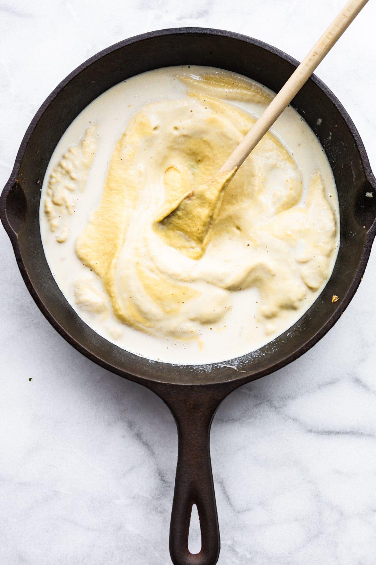 Stirring non dairy cream in with cauliflower