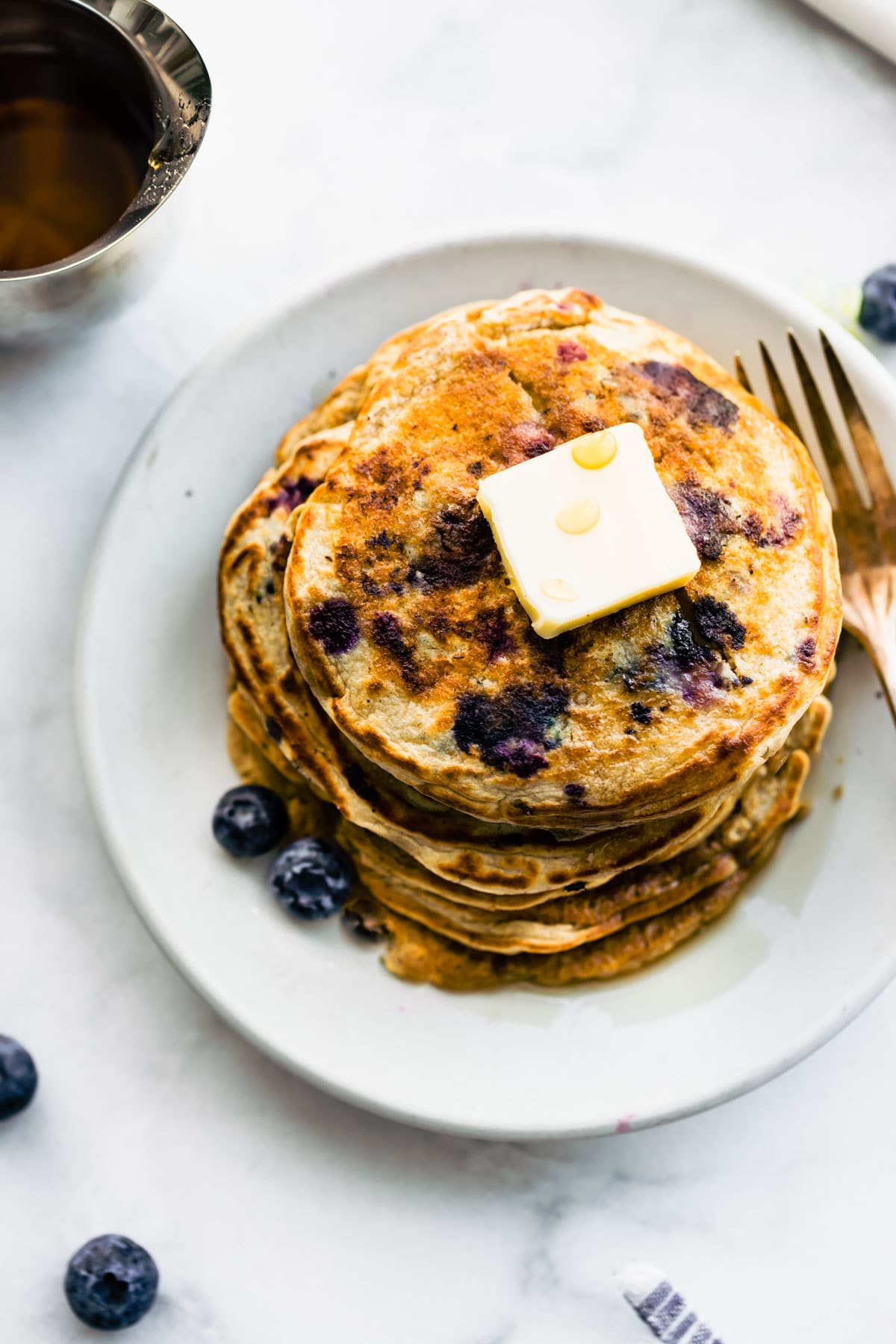 overhead: large stack of blueberry vegan protein pancakes with pat of butter on top