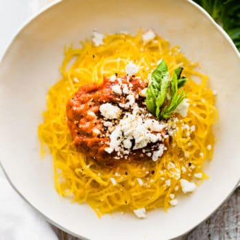 plate of Instant Pot spaghetti squash pasta with nomato sauce and dairy free Parmesan cheese