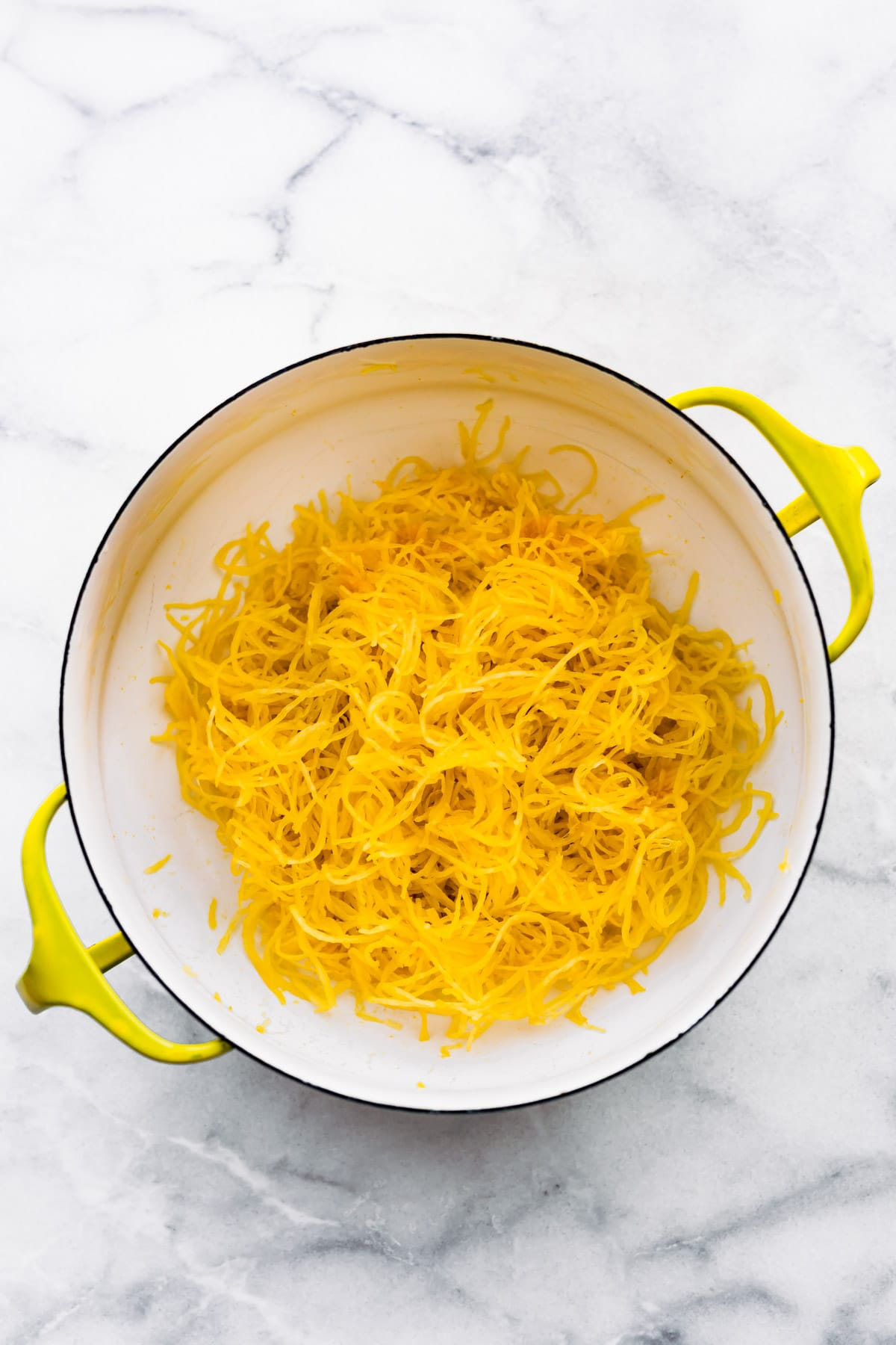 overhead: strands of spaghetti squash in large white pot with yellow handles