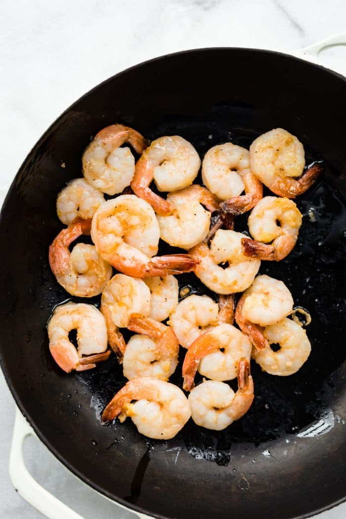 shrimp sauteing in skillet with oil