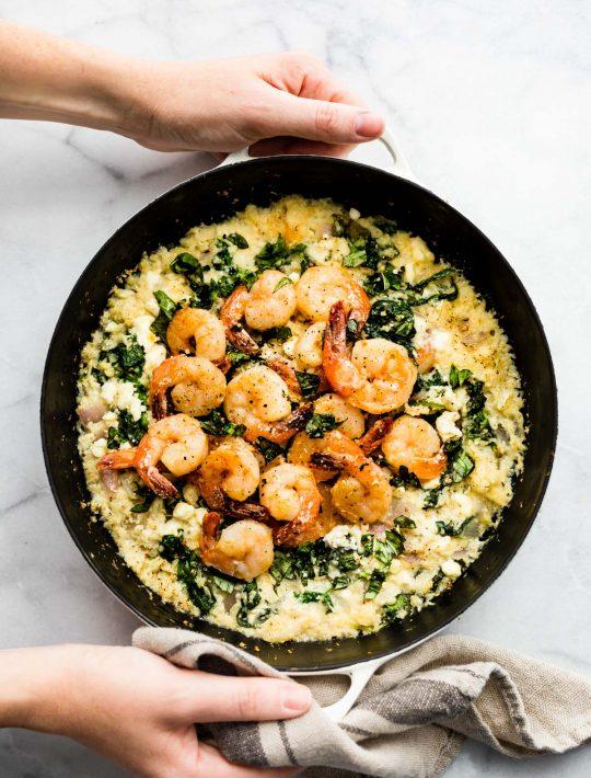hero shot: woman's hands holding pan of cauliflower risotto shrimp skillet